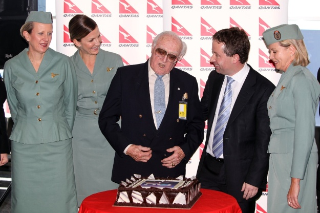 "The small ceremony was held at the gate prior to the departure of QF 73 to San Francisco.  A cake, bearing the same design as the TV monitor screen, was cut by Val St Leon, a QF Boeing 707 captain of the time. He is accompanied by Alan Joyce, CEO, and some ""hostesses"" wearing uniforms of the period.  Copyright Photo: John Adlard."