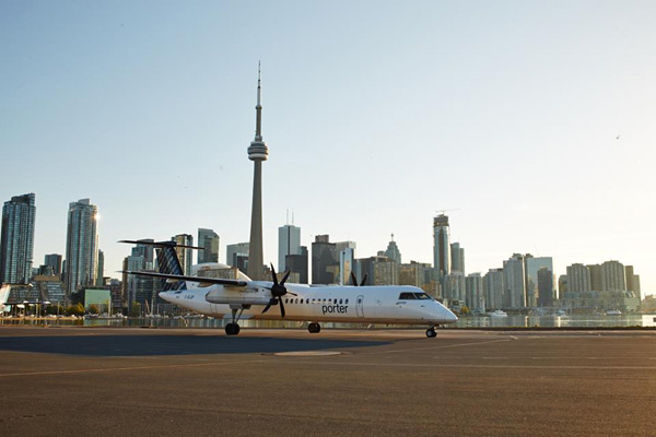 Porter DHC-8-400 at Billy Bishop with Toronto city skyline (Porter)(LR)
