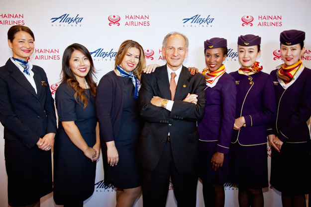Assistant Editor Joel Chusid surrounded by Alaska Airlines and Hainan Airlines Flight Attendants